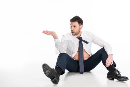 Photo for Overweight man in tight formal wear gesturing with hand while sitting on white with copy space - Royalty Free Image