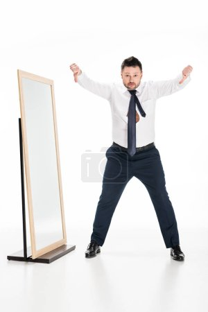 Photo for Overweight man in formal wear showing thumbs down near mirror on white - Royalty Free Image