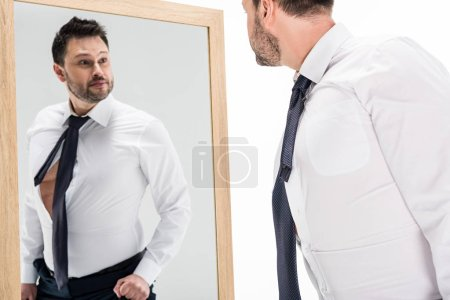 Photo for Overweight man in formal wear looking at reflection in mirror isolated on white - Royalty Free Image