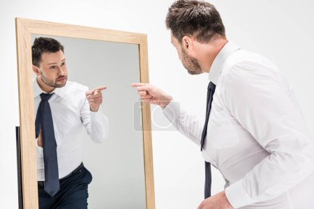 overweight man in formal wear pointing with finger at reflection in mirror on white
