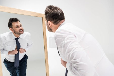 Photo for Angry overweight man in formal wear looking at reflection in mirror on white - Royalty Free Image