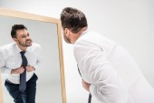 angry overweight man in formal wear looking at reflection in mirror on white