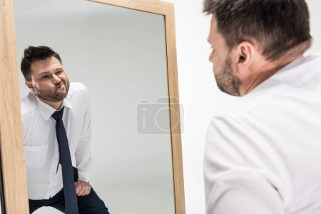 chubby man in formal wear looking at reflection in mirror isolated on white