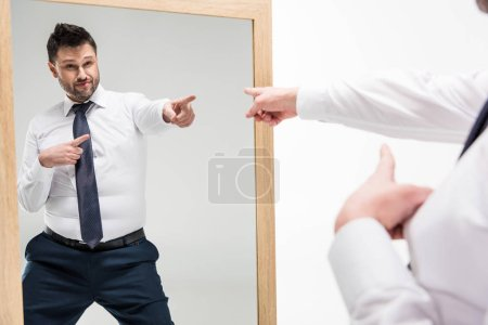 Foto de Overweight man in formal wear pointing with fingers while looking at mirror isolated on white - Imagen libre de derechos