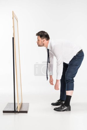 overweight man in formal wear bending over and looking at mirror on white