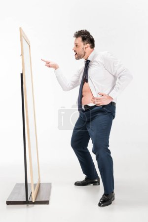 Photo for Overweight man in tight formal wear looking at mirror and pointing with finger on white - Royalty Free Image