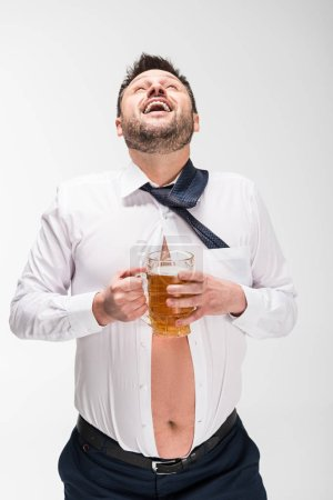 Photo for Happy overweight man in tight shirt laughing while holding glass of beer on white - Royalty Free Image