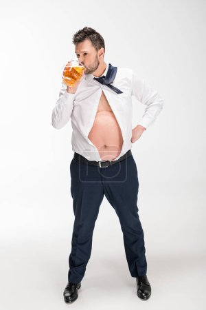 Photo for Overweight man in tight shirt drinking glass of beer on white - Royalty Free Image