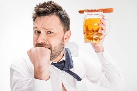 Photo for Handsome man biting fist and holding glass of beer with sausage isolated on white - Royalty Free Image
