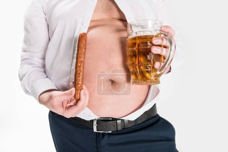 Photo for Partial view of overweight man showing belly and holding glass of beer with grilled sausage isolated on white - Royalty Free Image