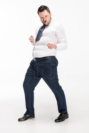 Foto de Overweight man in tight formal wear pointing with fingers and looking at camera on white - Imagen libre de derechos