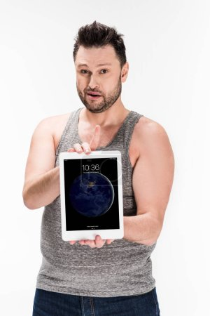 Photo for Overweight man looking at camera and showing digital tablet with apple home screen isolated on white - Royalty Free Image