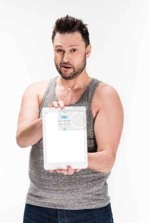 Photo for Overweight man looking at camera and showing digital tablet with skype app on screen isolated on white - Royalty Free Image