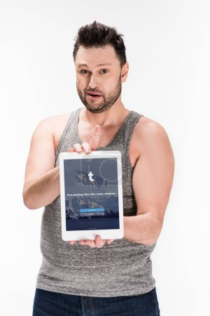 Photo for Overweight man looking at camera and showing digital tablet with tumblr app on screen isolated on white - Royalty Free Image