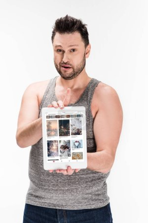 Photo pour Overweight man looking at camera and showing digital tablet with pinterest app on screen isolated on white - image libre de droit