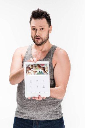 Photo pour Homme en surpoids regardant l'appareil photo et montrant tablette numérique avec application quadratique à l'écran isolé sur blanc - image libre de droit
