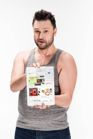 Photo pour Overweight man looking at camera and showing digital tablet with ebay app on screen isolated on white - image libre de droit