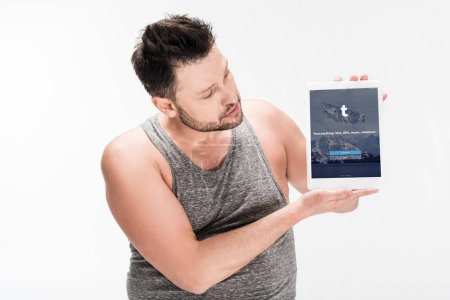 Photo for Overweight man showing digital tablet with tumblr app on screen isolated on white - Royalty Free Image