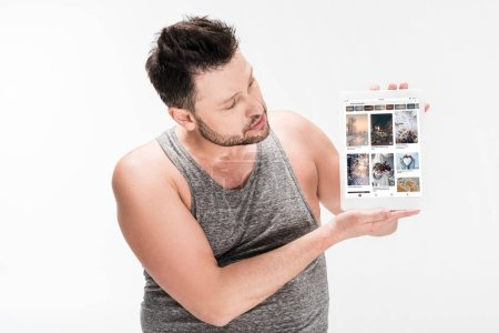 Photo for Overweight man showing digital tablet with pinterest app on screen isolated on white - Royalty Free Image