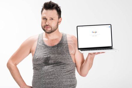Photo for Overweight man looking at camera and holding laptop with google website on screen isolated on white - Royalty Free Image