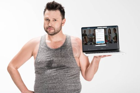Photo for Overweight man looking at camera and holding laptop with linkedin website on screen isolated on white - Royalty Free Image