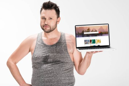 Photo for Overweight man looking at camera and holding laptop with shutterstock website on screen isolated on white - Royalty Free Image