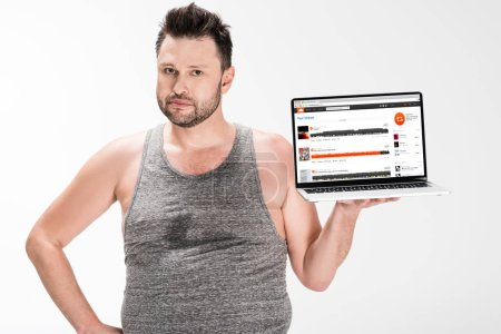 Photo for Overweight man looking at camera and holding laptop with soundcloud website on screen isolated on white - Royalty Free Image