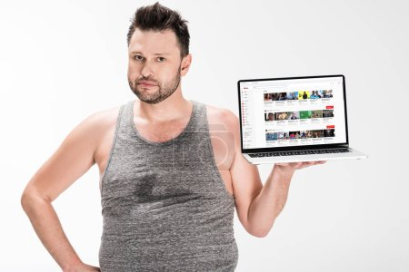 Photo for Overweight man looking at camera and holding laptop with youtube website on screen isolated on white - Royalty Free Image