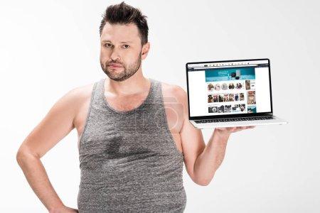 Photo pour Homme en surpoids regardant la caméra et tenant ordinateur portable avec site amazone à l'écran isolé sur blanc - image libre de droit