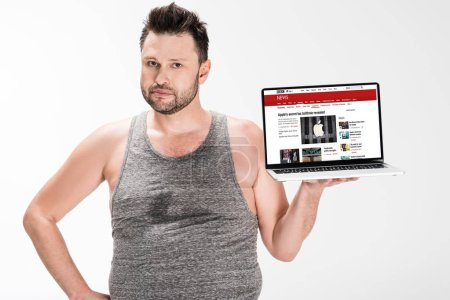 Photo pour Overweight man looking at camera and holding laptop with bbc news website on screen isolated on white - image libre de droit