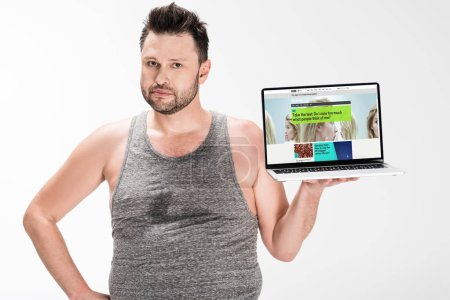 Photo for Overweight man looking at camera and holding laptop with bbc website on screen isolated on white - Royalty Free Image