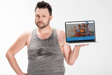 Photo for Overweight man looking at camera and holding laptop with couchsurfing website on screen isolated on white - Royalty Free Image
