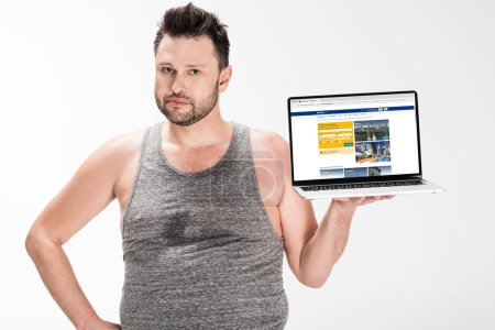 Photo for Overweight man looking at camera and holding laptop with booking website on screen isolated on white - Royalty Free Image