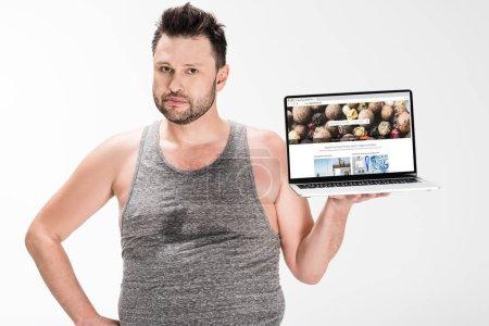Photo pour Homme en surpoids regardant l'appareil-photo et retenant l'ordinateur portatif avec le site Web de depositphotos sur l'écran isolé sur le blanc - image libre de droit