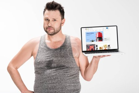 Photo for Overweight man looking at camera and holding laptop with ebay website on screen isolated on white - Royalty Free Image