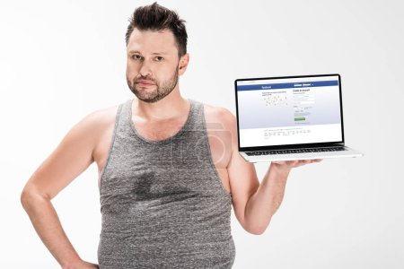 Foto de Overweight man looking at camera and holding laptop with facebook website on screen isolated on white - Imagen libre de derechos