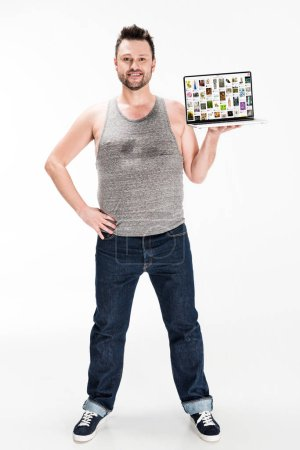 Photo for Smiling overweight man looking at camera and presenting laptop with pinterest website on screen isolated on white - Royalty Free Image