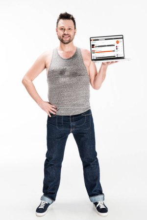 Photo for Smiling overweight man looking at camera and presenting laptop with soundcloud website on screen isolated on white - Royalty Free Image