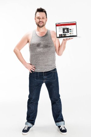 Photo for Smiling overweight man looking at camera and presenting laptop with bbc news website on screen isolated on white - Royalty Free Image