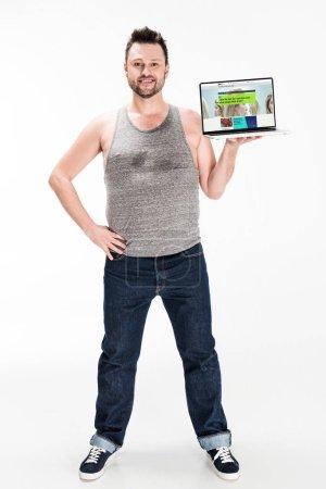 Photo pour Homme de poids excessif de sourire regardant l'appareil-photo et présentant l'ordinateur portatif avec le site Web de bbc sur l'écran isolé sur le blanc - image libre de droit