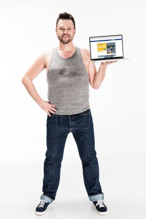 Photo for Smiling overweight man looking at camera and presenting laptop with booking website on screen isolated on white - Royalty Free Image
