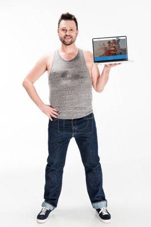Photo for Smiling overweight man looking at camera and presenting laptop with couchsurfing website on screen isolated on white - Royalty Free Image