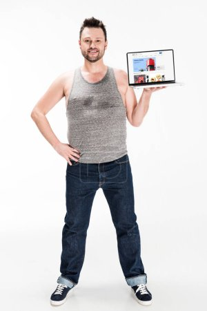 Photo pour Smiling overweight man looking at camera and presenting laptop with ebay website on screen isolated on white - image libre de droit