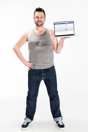 Photo pour Smiling overweight man looking at camera and presenting laptop with facebook website on screen isolated on white - image libre de droit
