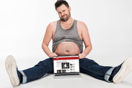 Photo for Skeptical overweight man making facial expression and sitting with laptop with bbc news website on screen isolated on white - Royalty Free Image
