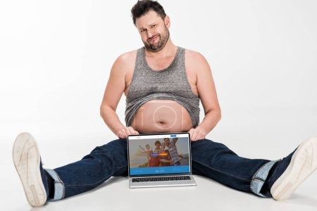 Photo for Skeptical overweight man making facial expression and sitting with laptop with couchsurfing website on screen isolated on white - Royalty Free Image