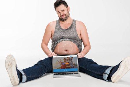 Photo pour Homme sceptique en surpoids faisant expression faciale et assis avec ordinateur portable avec site de couchsurfing à l'écran isolé sur blanc - image libre de droit
