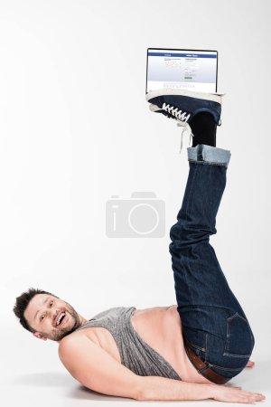 Photo pour Excité homme en surpoids regardant la caméra et tenant avec les jambes ordinateur portable avec facebook site à l'écran - image libre de droit