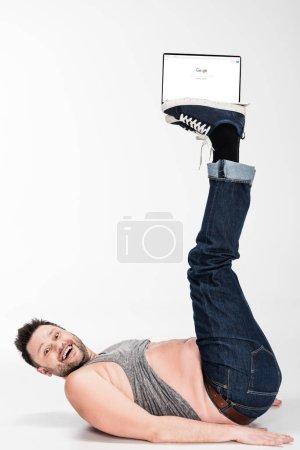 Photo pour Excité homme en surpoids regardant la caméra et tenant avec les jambes ordinateur portable avec google site Web à l'écran - image libre de droit
