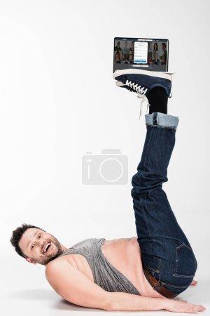 Photo pour Excité homme en surpoids regardant la caméra et tenant avec les jambes ordinateur portable avec linkedin site Web à l'écran - image libre de droit